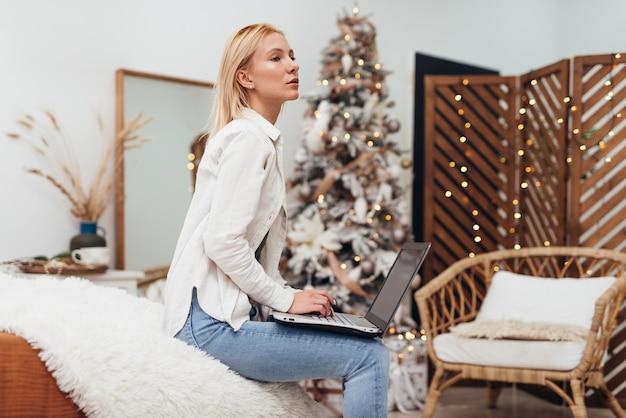 크리스마스 시간에 노트북을 가진 젊은 여자