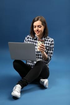 青でコーヒーを飲むラップトップを持つ若い女性