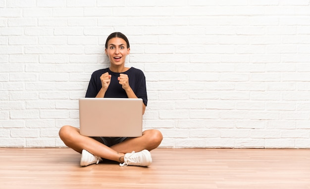 Young woman with a laptop sitting on the floor celebrating a victory