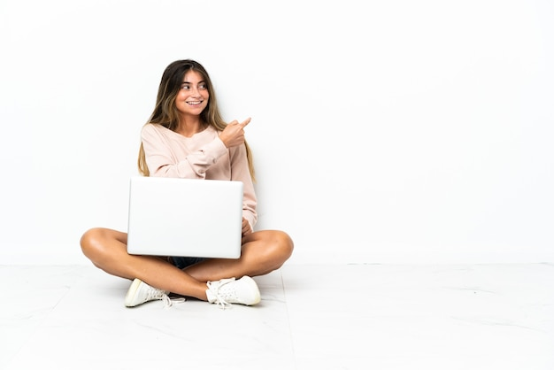 Young woman with a laptop sitting on the floor isolated on white background pointing back