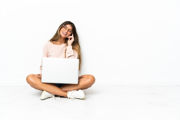 Young woman with a laptop sitting on the floor isolated on white background with glasses and happy