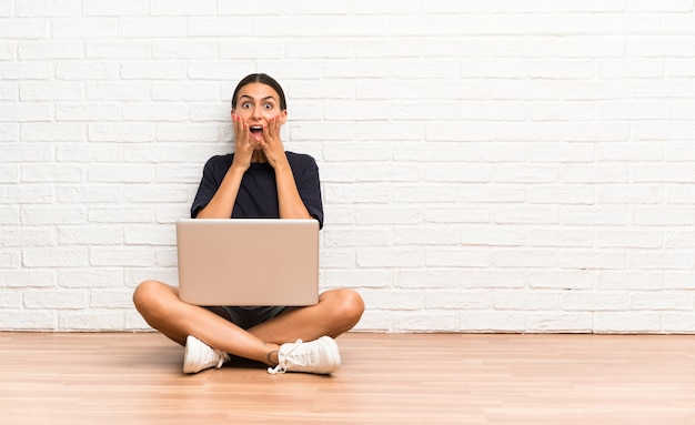 Young woman with a laptop sitting on the floor with surprise facial expression