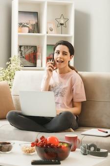 Молодая женщина с ноутбуком разговаривает по телефону, сидя на диване за журнальным столиком в гостиной