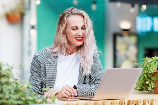 Young woman with laptop in a summer street cafe. beautiful smiling blonde with long hair.