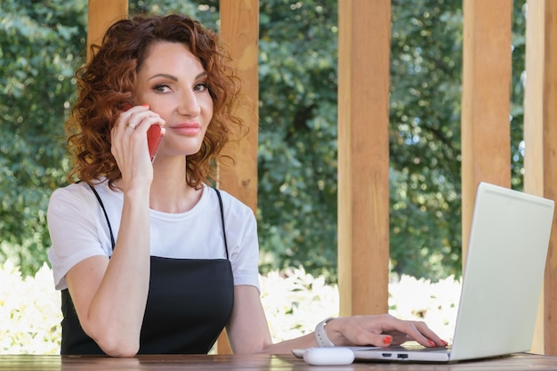 Young woman with laptop talks on a mobile phone woman freelancer is in business negotiations