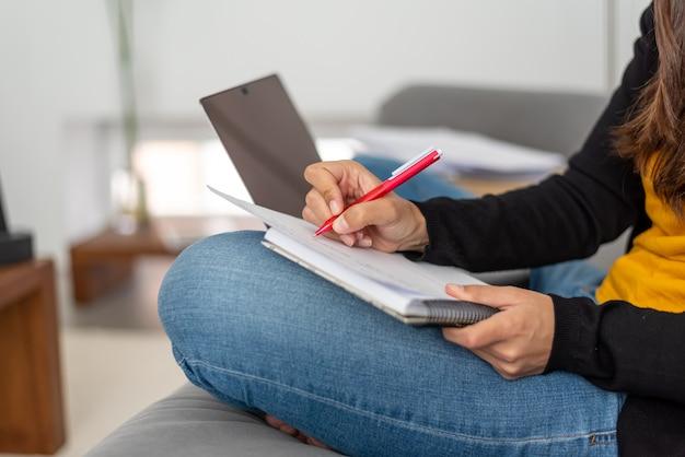 彼女の家のソファーで在宅勤務のラップトップを持つ若い女性