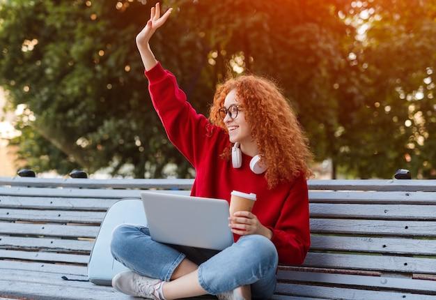 手を振ってラップトップを持つ若い女性