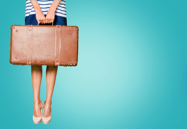 Young woman with leather suitcase on bright blue background, travelling concept