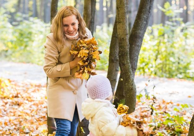 그녀의 손에 잎을 가진 젊은 여자. 가을 10 월 배경