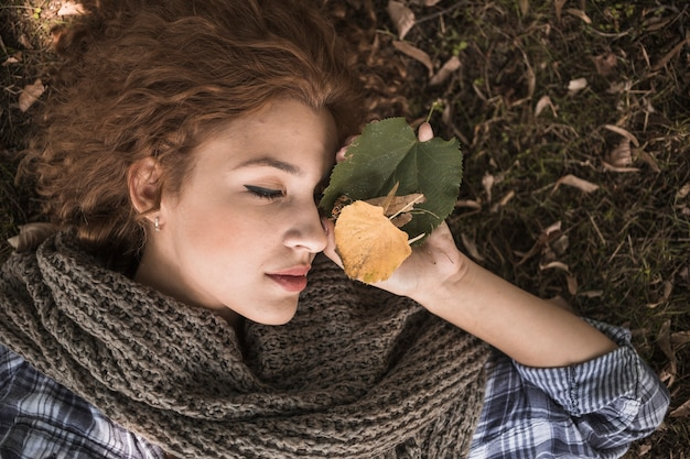 Young woman with leaves sleeping on ground