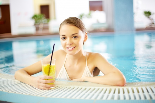 Young woman with a lemonade in the swimming pool