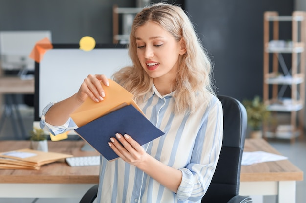 オフィスで手紙を持つ若い女性