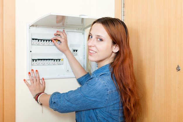 Young woman with light-switch in home
