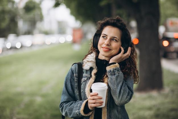 Молодая женщина с прослушивания музыки и пить кофе