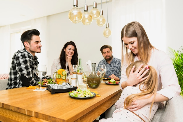 Young woman with little daughter and friends sitting at table