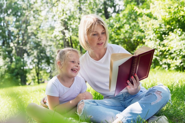A young woman with a little daughter lie in the park on the grass and read a book. pretty blonde with freckles on her face. camping on a sunny summer day.
