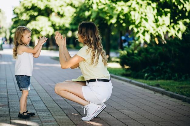 公園を歩いて小さな娘を持つ若い女性