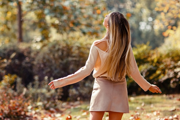 Young woman with long blonde hair dancing in the park