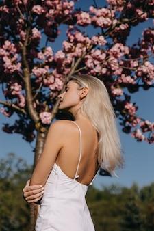 花の背景に桜の木の公園で屋外で長いブロンドの髪を持つ若い女性