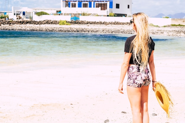 Молодая женщина с длинными светлыми волосами, глядя со спины, смотрит на пляж с белым песком и прозрачную океанскую карибскую морскую воду во время летних каникул.