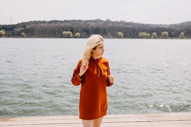 湖のほとりに風の中に立つ長い赤いパーカーを着た長いブロンドの髪を持つ若い女性