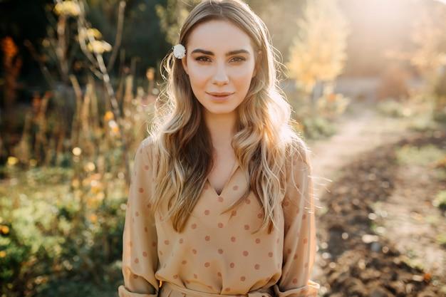 カメラを見て日没時に長いブロンドのウェーブのかかった髪の若い女性