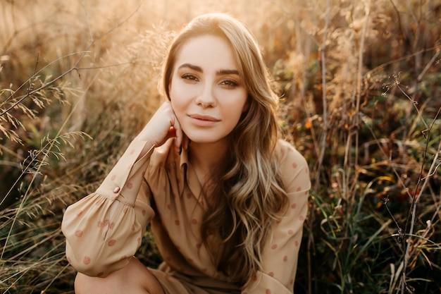 背の高い乾いた草のフィールドに座って笑っている長いブロンドのウェーブのかかった髪の若い女性