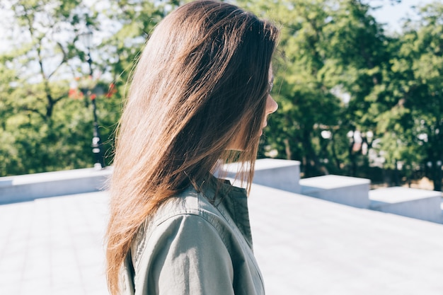 Young woman with long brown hair walks in the park in summer