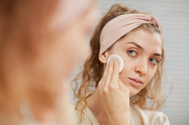 鏡の前に立っているスポンジで顔を掃除する長い巻き毛の若い女性