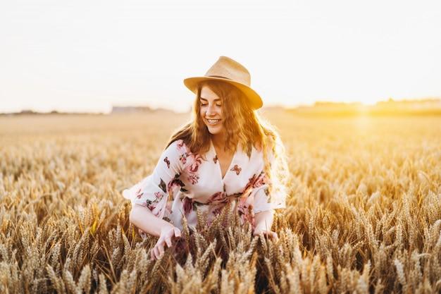 麦畑の中に立っている花柄の明るい白いドレスの帽子の長い巻き毛とそばかすの顔を持つ若い女性