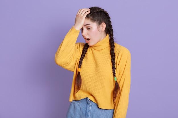 Молодая женщина с длинными темными волосами и косичками стоит с раскрытым ртом, держа руку на лбу