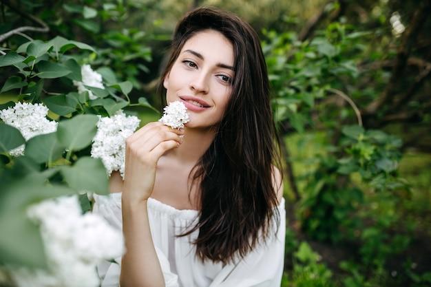 白いライラックの花と長い黒髪の若い女性