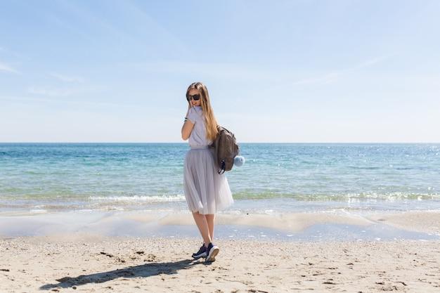 長い髪と海の近くの背中にバッグを持つ若い女性