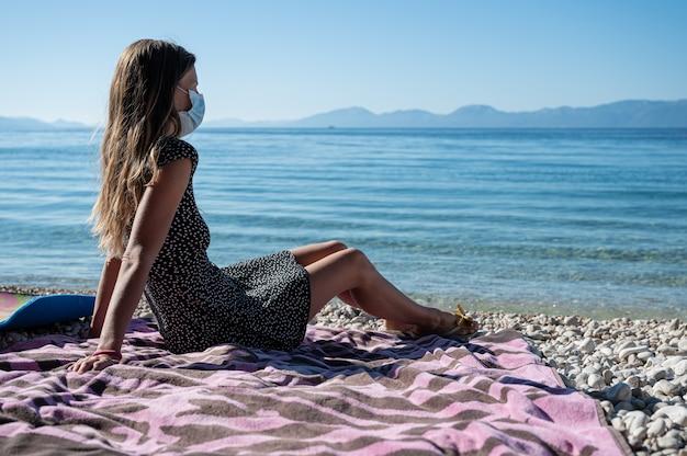 Молодая женщина с длинными волосами и пятнистым платьем сидит на галечном пляже, глядя вдаль, в медицинской защитной маске.