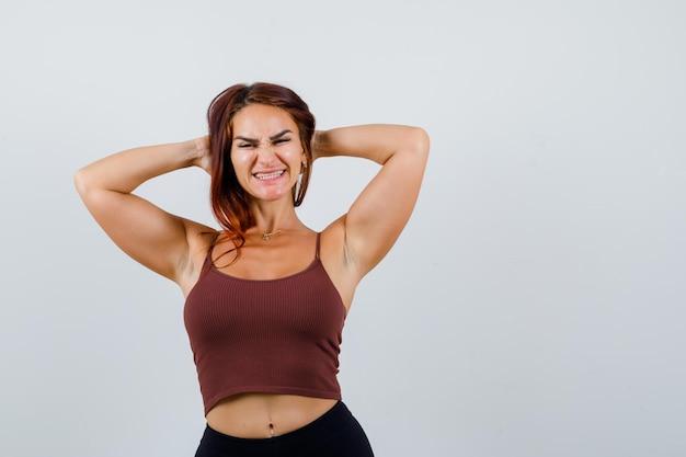Giovane donna con i capelli lunghi in un top corto marrone