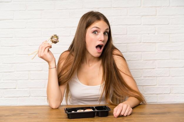Молодая женщина с длинными волосами, едят суши