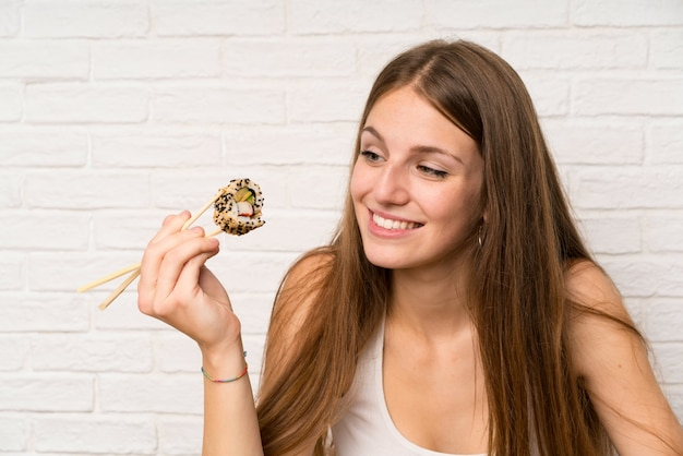 Young woman with long hair eating sushi