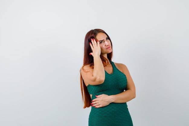 Giovane donna con i capelli lunghi in un bodycon verde