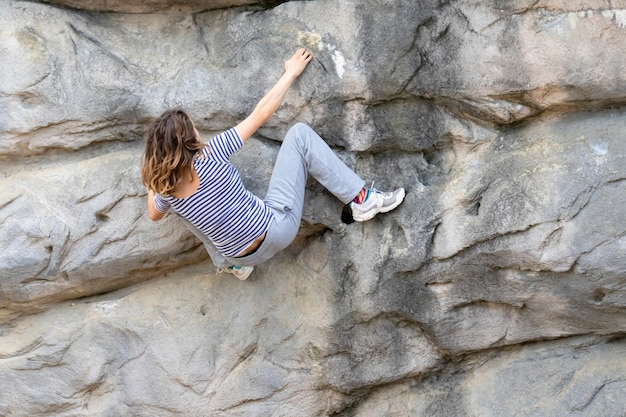 Young woman with long hair hanging on a rocky face of a mountain while climbing up without a rope support