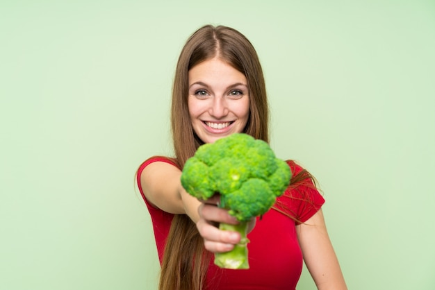 Young woman with long hair holding a broccoli