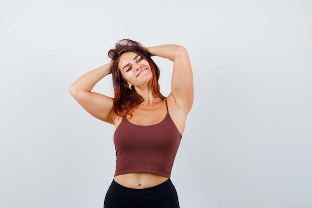 茶色のクロップトップで長い髪の若い女性