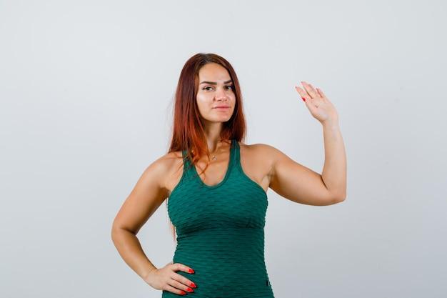 녹색 bodycon에 긴 머리를 가진 젊은 여자