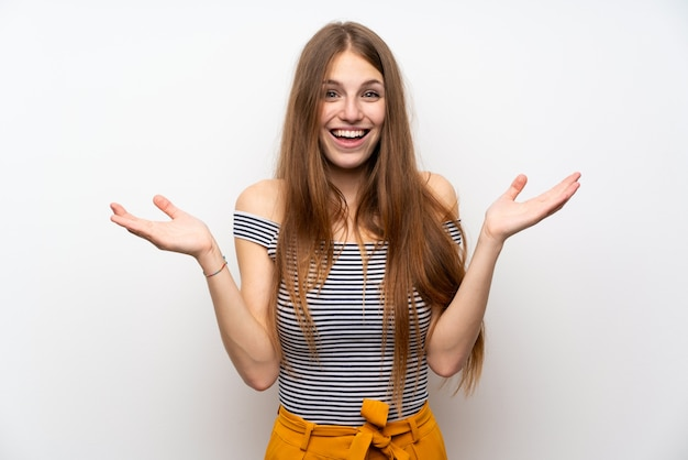 Young woman with long hair over isolated white wall with shocked facial expression