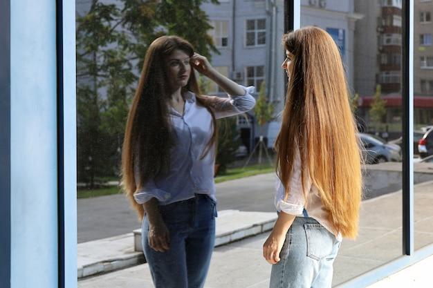 長い髪の若い女性は、ガラスの建物の反射で自分自身を見ています