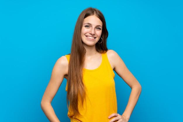 笑って孤立した青い壁の上の長い髪を持つ若い女