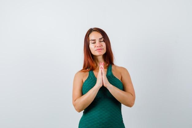 Giovane donna con i capelli lunghi che prega