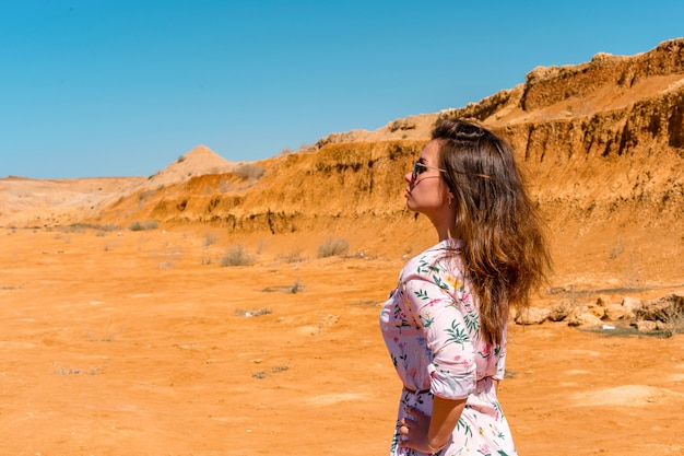 A young woman with long hair in a short dress walks through the orange rocky desert on a hot day
