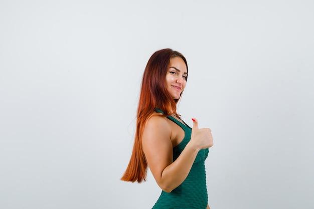 Молодая женщина с длинными волосами показывает палец вверх