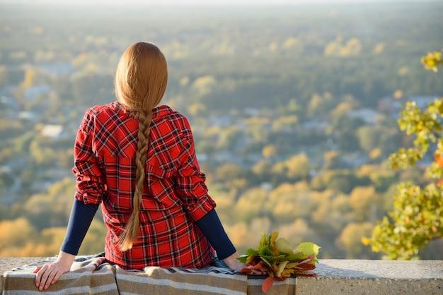 Молодая женщина с длинными волосами сидит на холме с видом на город. вид сзади