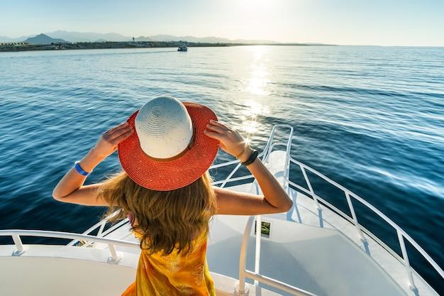 푸른 바다의 전망을 즐기는 요트 갑판에 서있는 긴 머리를 가진 젊은 여자